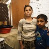 Kosovo / Returnee Roma woman Fatima Marolli in her kitchen with son Shemsechir, in Vranjevac Roma community, Pristina. She is 40 years old, a widow, her husband was killed in conflict in June 1999, body was never found. She has three children - 23, 20 and 10. They returned home in 2002 to a newly built house. UNHCR co-ordinated the reconstruction, the donor was Swedish government. Her life is hard, she has no income, no job, receives 60 euros a month social assistance. She is not well, can't work, sons are not in good health either.The house is not very good, too small, walls are cracking, roof is leaking. They don't pay rent but have to pay utilities. But they don't pay because they don't have the money. They are at risk of being cut off from social assistance because she has grown-up sons. / UNHCR / L. Taylor / 6 August 2008