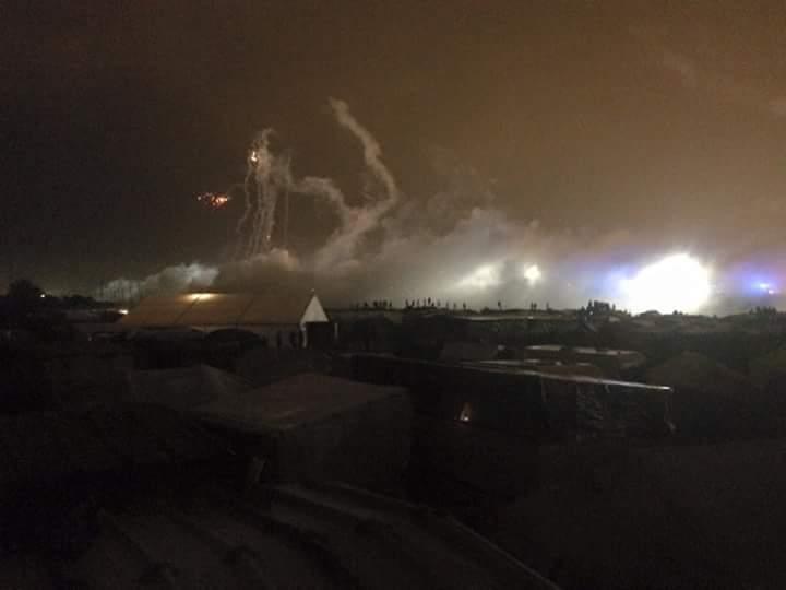 Au fond la rocade portuaire et les spots des projecteurs de la police. Les tirs de grenades dans le ciel et les nuages de gaz au sol. Photo prise par des militant-e-s calaisien-ne-s.